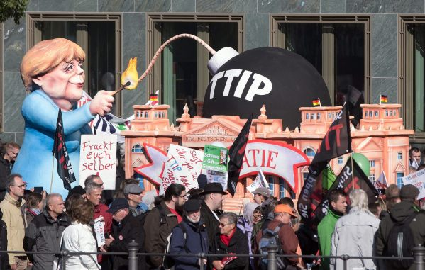 CAR007. Berlin (Germany), 10/10/2015.- A float created by float builder Jacques Tilly and depicting German Chancellor Angela Merkel igniting a 'TTIP bomb' accompanies a rally against the trade agreements TTIP and CETA in Berlin, Germany, 10 October 2015. More than 50,000 protesters were expected at Berlin's main train station on Saturday as part of a nationwide protest in Germany against the historic free trade agreements the European Union is negotiating with the United States and Canada. The Stop TTIP CETA rally has been called to oppose the EU's Transatlantic Trade and Investment Partnership (TTIP) with the US and the Comprehensive Economic and Trade Agreement (CETA) with Canada. (Protestas, Alemania, Estados Unidos) EFE/EPA/JOERG CARSTENSEN
